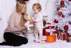 Шикарная мать при длинные светлые волосы представляя с прелестным милым d Стоковое Фото