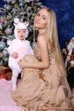 Шикарная мать при длинные светлые волосы представляя с прелестным милым d Стоковые Изображения RF
