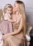 Шикарная мать при длинные светлые волосы представляя с прелестным милым d Стоковое фото RF