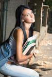 Шикарная молодая девушка студента брюнет outdoors. Стоковое Фото
