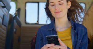 Шикарная молодая женщина отправляя SMS на мобильном телефоне в фургоне 4k акции видеоматериалы