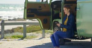 Шикарная молодая женщина отправляя SMS на мобильном телефоне в фургоне 4k сток-видео