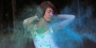 Шикарная молодая женщина при короткие волосы представляя с взрывать Holi стоковые изображения