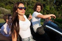 Шикарная молодая темн-с волосами женщина в солнечных очках с молодым человеком сидит в черном cabriolet на солнечный день стоковая фотография rf