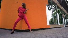 Шикарная молодая дама в красном костюме на представлять высоких пяток акции видеоматериалы