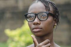 Шикарная молодая африканская девушка в eyeglasses думая outdoors с запачканной предпосылкой Стоковые Изображения