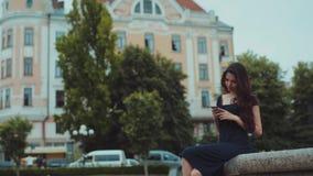 Шикарная молодая женщина брюнет в длинном вскользь черном платье сидит на фонтане и активно использует ее телефон для беседовать видеоматериал