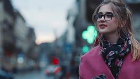 Шикарная молодая женщина в элегантном взгляде идя вниз с толпить улицы города, с чашкой кофе и используя телефон многодельно сток-видео