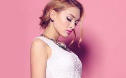 Шикарная молодая женщина с белокурым вьющиеся волосы и нежным составом, в элегантных одеждах с аксессуарами стоковые фотографии rf