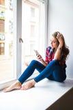 Шикарная молодая женщина с длинными красными волосами проверяя электронную почту и посылая сообщение sms на мобильном телефоне Стоковое Фото