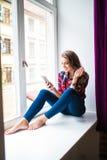 Шикарная молодая женщина с длинными красными волосами проверяя электронную почту и посылая сообщение sms на мобильном телефоне Стоковая Фотография RF