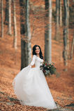 Шикарная невеста брюнет в элегантном платье держа букет представляя около леса и озера стоковое изображение rf