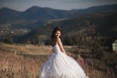 Шикарная невеста в элегантном платье представляя на солнечном летнем дне на предпосылке гор Стоковое Изображение