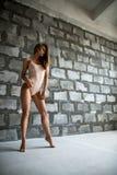 Шикарная сексуальная блондинка в бежевом теле каменной стеной Стоковые Фото