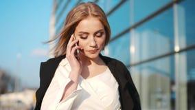 Шикарная стильная молодая женщина в элегантном обмундировании проходя крупный аэропорт и говоря на телефоне солнечная погода акции видеоматериалы