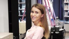 Шикарная счастливая молодая женщина с совершенными длинными сияющими волосами усмехаясь на салоне парикмахера стоковое изображение