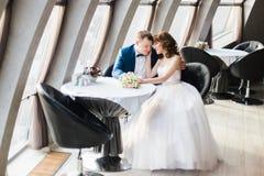 Шикарная счастливая коричневая невеста волос и элегантный groom в голубом костюме обнимая сидеть в ресторане стоковая фотография