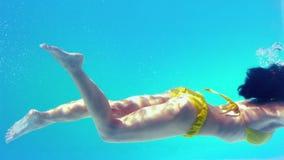 Шикарное брюнет в желтом бикини плавая под водой видеоматериал