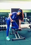 Шикарное брюнет в sportswear поднимая некоторые весы и работу Стоковое Изображение