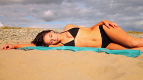 Шикарное брюнет лежа на пляже на шарфе акции видеоматериалы