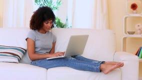 Шикарное жизнерадостное брюнет сидя на кресле используя компьтер-книжку акции видеоматериалы