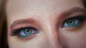 Шикарные голубые и зеленые глаза кавказской женщины смотря сконцентрированную камеру и показывая красивые косметики внутри помеще видеоматериал