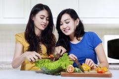 Шикарные девушки варя салат в кухне Стоковые Фотографии RF