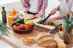 Шикарные молодые женщины подготавливая обедающий в кухне Стоковые Изображения