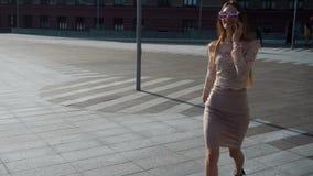 Шикарные молодые прогулки бизнес-леди и говоря телефон акции видеоматериалы