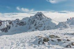 Шикарный ландшафт горы зимы с группой в составе hikers взбираясь на верхней части Стоковая Фотография