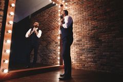 шикарный взгляд Во всю длину красивого костюма человека полностью регулируя его куртку пока стоящ перед зеркалом стоковая фотография rf