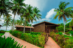 Шикарный взгляд дома бунгала стоя над землей перед пляжем с видом на океан на немножко пасмурном da Стоковые Изображения RF