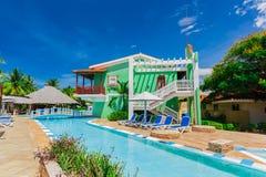 шикарный изумительный взгляд колониальных земель гостиницы, красивого приглашая бассейна и ретро стильных зданий на голубом небе Стоковые Изображения