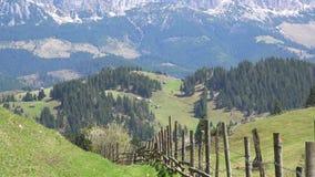 Шикарный ландшафт весны, деревянная загородка, зеленая трава, белые идти снег горы акции видеоматериалы