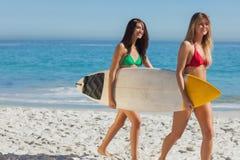 2 шикарных женщины в бикини держа surfboard Стоковое фото RF