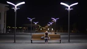 Шина замороженной дамы ждать последняя на пустой станции ночи, проверяя расписание видеоматериал