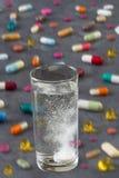 Шипучая таблетка в воде с пузырями с пестроткаными пилюльками и капсулами на серой предпосылке шифера Стоковые Фото