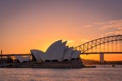 Широкая съемка моста оперного театра и гавани Сиднея, silhouetted против a стоковое фото