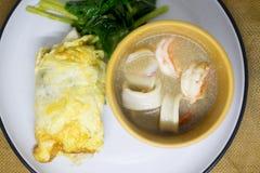 Широкие лапши риса обернутые яичком служили с морепродуктами в подливке стоковое фото