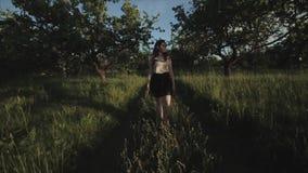 Широкий взгляд красивой девушки p брюнета в одеждах лета элегантных против зеленые деревья Счастливая элегантная девушка в лесе сток-видео