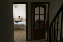Широкий взгляд женщины работая с компьтер-книжкой в спальне дома и Стоковая Фотография