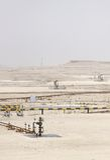 Широкий взгляд wellhead & масляных насосов масла в обширном выходе на поверхность месторождения нефти Бахрейна Стоковые Фотографии RF