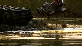 Широкое ведро экскаватора выкапывает вверх почву от дна реки на заходе солнца Очищать и углублять  сток-видео