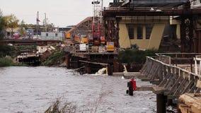 Широкое река с районом строительства моста с огромными конкретными beems и кранами акции видеоматериалы