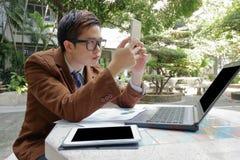 Широкоформатная съемка красивого бизнесмена смотря его smartphone для его работы в парке outdoors стоковая фотография