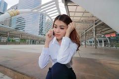 Широкоформатная съемка молодого привлекательного азиатского работника офиса говоря на телефоне на внешней предпосылке офиса Стоковое Изображение