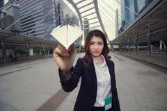 Широкоформатная съемка привлекательной молодой азиатской коммерсантки держа самолет бумаги в ее руке зрение лупы диаграммы принци стоковые изображения