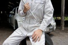 Широкоформатная съемка профессионального механика в равномерных ключе и автошине удерживания на предпосылке гаража ремонта Концеп Стоковые Изображения RF