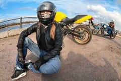Широкоформатный всадника мотоцикла девушки сидя на земле рядом с велосипедом и женским велосипедистом с тяпкой на предпосылке Стоковые Изображения RF