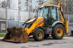 Широко распространённая модель всеобщего затяжелителя backhoe JCB Компании Великобритании узнаваемого желтого цвета стоковые фото
